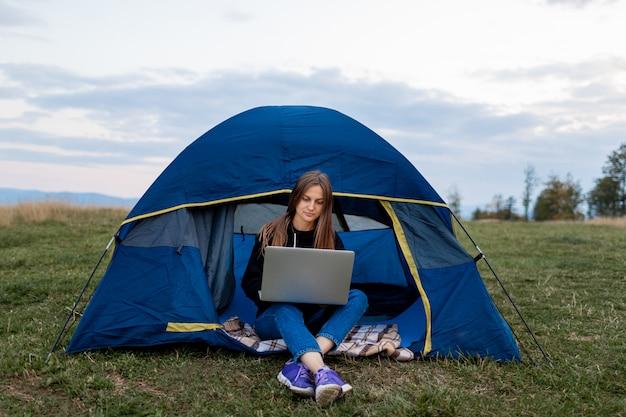 Fille avec ordinateur portable dans les montagnes. femme de tourisme utilise un ordinateur portable dans la nature, pigiste tapant sur un ordinateur près d'une tente dans un voyage