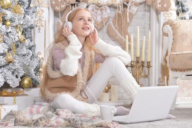 Fille avec ordinateur portable écoutant de la musique près de l'arbre de noël