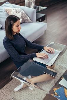 Fille avec un ordinateur portable est assise à la maison sur le sol.
