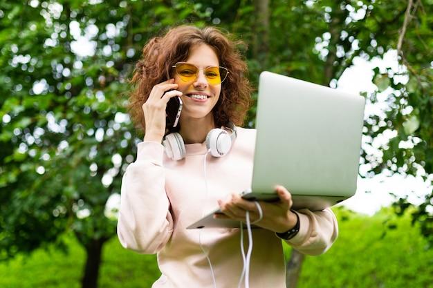 Fille avec un ordinateur portable fait un appel téléphonique dans un parc verdoyant de la ville. concept indépendant