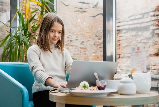 Fille avec un ordinateur portable à une table dans un café.
