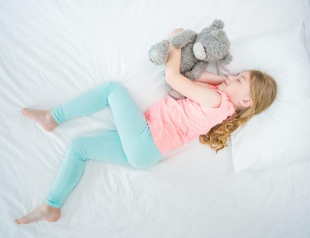 La fille avec un ours en peluche dormant sur le lit. vue d'en-haut