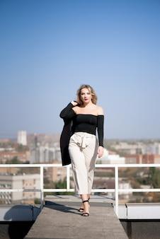 Une fille en pantalon beige et veste noire marche sur le toit de la maison.