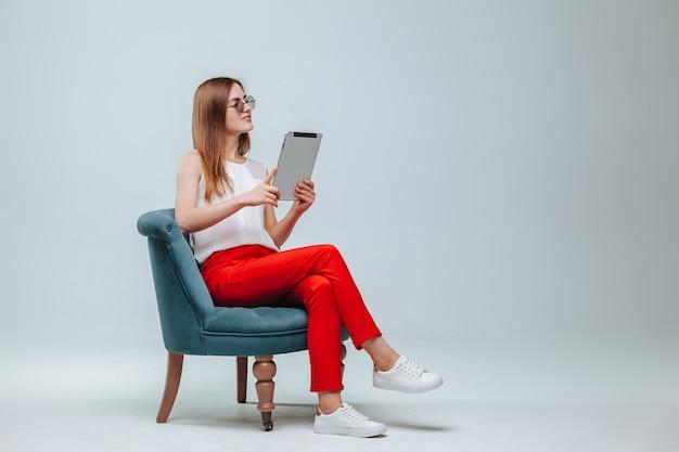 Fille en pantalon rouge assise sur une chaise et utilisant sa tablette