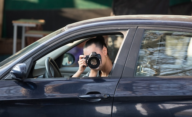 Fille papparazi avec un appareil photo dans la voiture