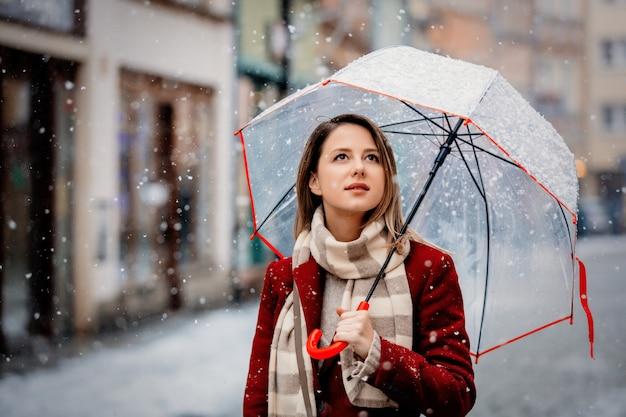 Fille avec un parapluie blanc qui tombe et reste dans la rue