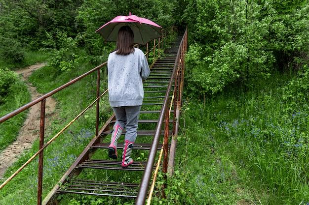 Une fille avec un parapluie marche dans les bois par temps de pluie