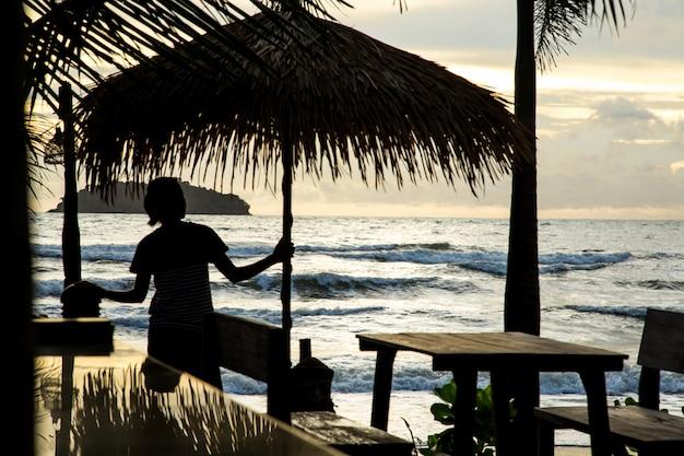 Fille avec un parapluie sur la plage au coucher du soleil