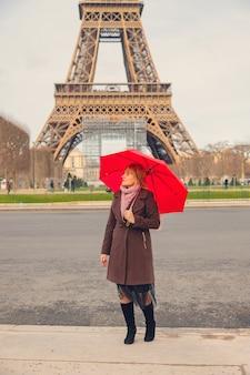 Fille avec un parapluie rouge près de la tour eiffel à paris. mise au point sélective.