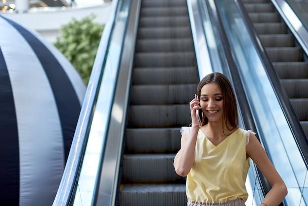 Fille parlant au téléphone dans le centre commercial escalade l'escalator