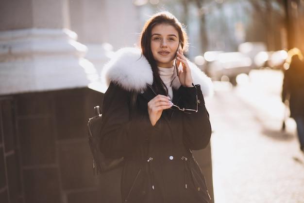 Fille parlant au téléphone dans la rue par centre d'affaires