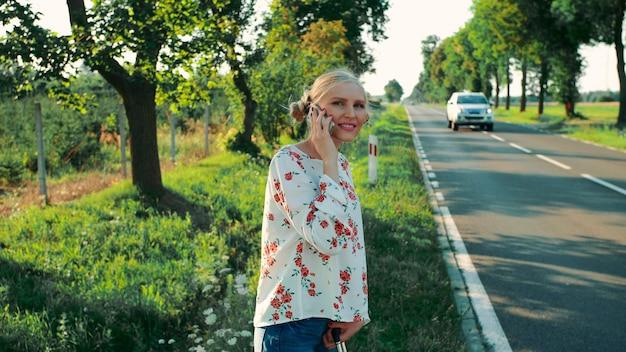Fille parlant au téléphone en faisant de l'auto-stop vue latérale d'une jolie jeune femme parlant sur smartphone et ...