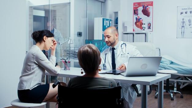 Fille parlant avec un médecin du rétablissement d'une mère âgée en fauteuil roulant. invalidité handicapée traitement des personnes âgées handicapées dans un hôpital ou une clinique privé moderne. médecine et système de santé