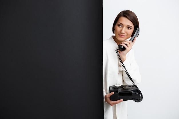 Fille parlant sur vieux téléphone sur mur noir et blanc