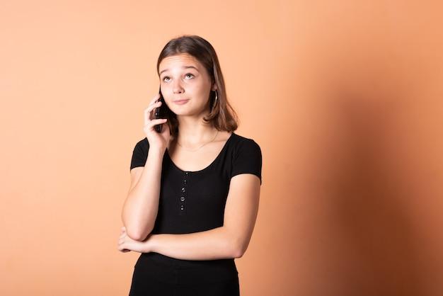 La fille parle au téléphone avec surprise, sur fond orange clair. pour n'importe quel but.