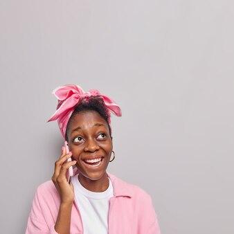 Fille parle sur téléphone mobile a une expression positive répond aux appels téléphoniques meilleur ami via cellulaire porte un foulard rose attaché sur la tête se tient à l'intérieur