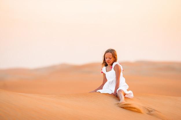 Fille parmi les dunes dans le désert aux emirats arabes unis