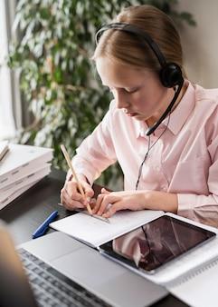 Fille participant à un cours en ligne tout en prenant des notes