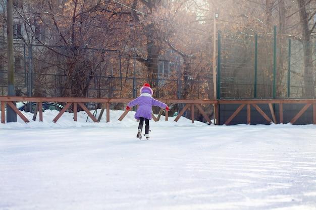 Une fille patine sur une patinoire en hiver. patinoire dans la cour de la ville. l'enfant apprend à patiner