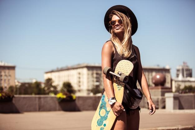 La fille patine sur une planche à roulettes
