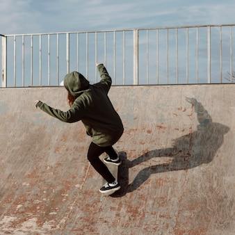 Fille de patineur à l'aide de rampes pour des figures