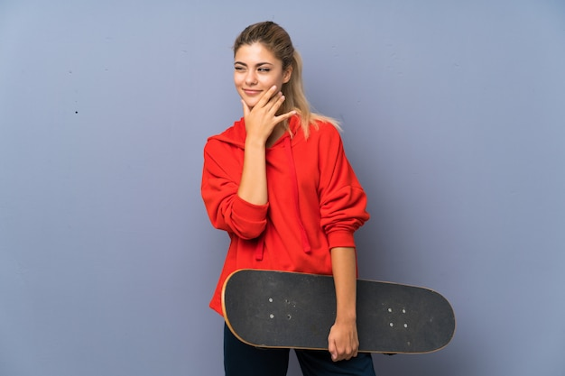 Fille de patineur blonde adolescente sur mur gris, pensant une idée