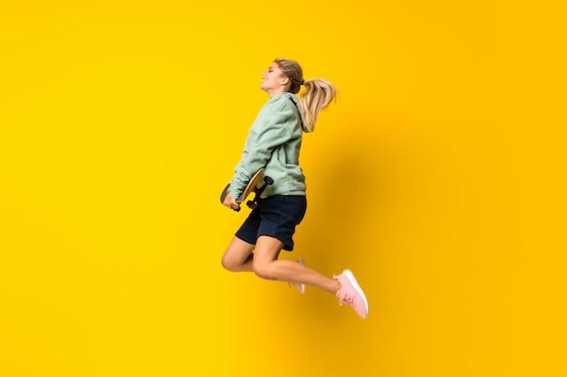 Fille de patineur blonde adolescente sautant sur fond jaune isolé