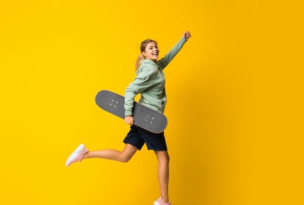 Fille de patineur blonde adolescente sautant par-dessus isolé jaune
