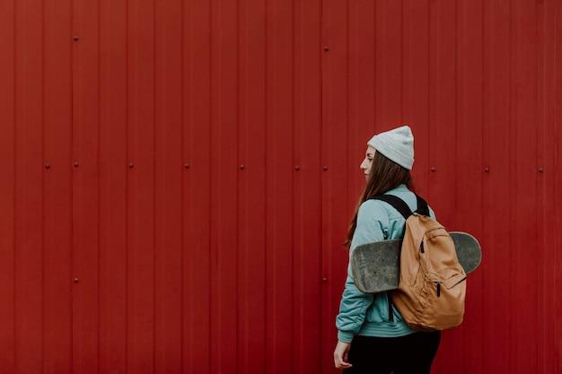 Fille de patineur dans le sac à dos de tenue urbaine et skate