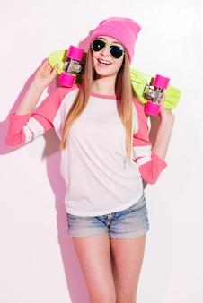 Fille de patineur heureux. jeune femme espiègle en chapeaux roses et lunettes de soleil tenant une planche à roulettes sur ses épaules en se tenant debout sur fond blanc