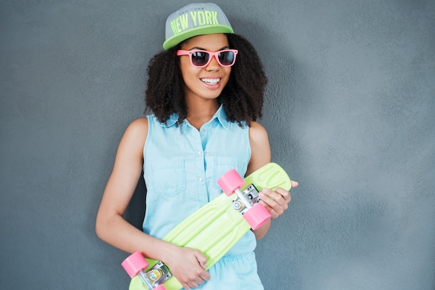 Fille de patineur. jolie jeune femme africaine tenant une planche à roulettes colorée et souriante en se tenant debout sur fond gris