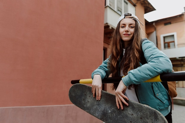 Fille de patineur en plein air et sa planche à roulettes