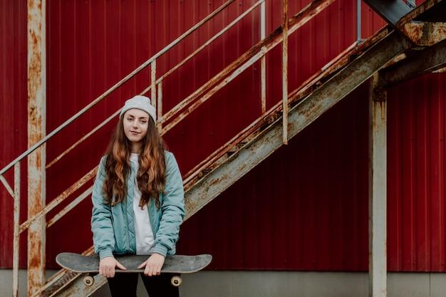 Fille de patineur tenant sa planche à roulettes devant elle