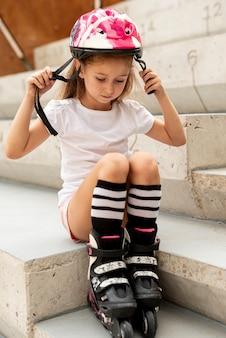 Fille avec patins à roues alignées et casque