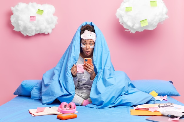 Une fille a une pause-café regarde l'écran du smartphone lit des nouvelles choquantes sur les réseaux sociaux enveloppée dans une couverture chaude aime l'atmosphère domestique est assise les jambes croisées sur le lit étudie à distance