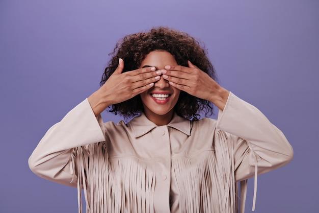 Une fille à la peau foncée en tenue beige sourit et ferme les yeux