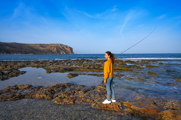 Fille de pêcheur à la ligne sur la plage de javea en méditerranée
