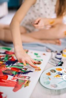 Fille peignant avec les doigts sur une grande toile au sol