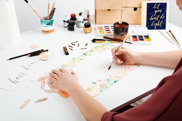 Fille peignant des fleurs sur papier avec aquarelle.