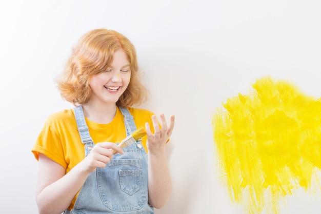 Fille peint un mur blanc en jaune