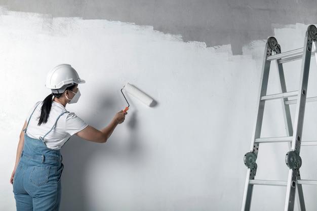 Fille peint un mur blanc avec un rouleau. réparation de l'intérieur. jeune décoratrice peignant un mur dans la pièce vide, concept builder ou peintre en casque avec rouleau à peinture sur la pièce vide.