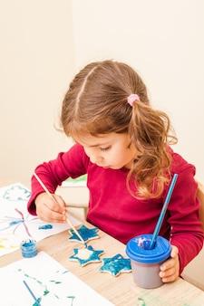 La fille peint avec un pinceau et des aquarelles sur des figures d'argile. décorations de vacances faites à la main