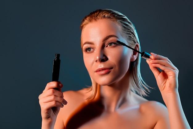 La fille peint ses cils avec du mascara.