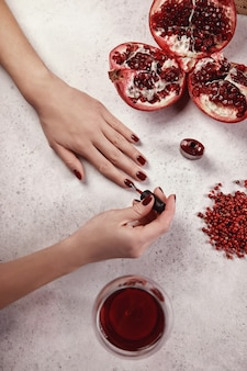 Fille peint ses ongles le gel polonais. fond blanc, verre de vin, détails rouges. belle main. extension des ongles. manucure, salon de spa. créatif, publicitaire.