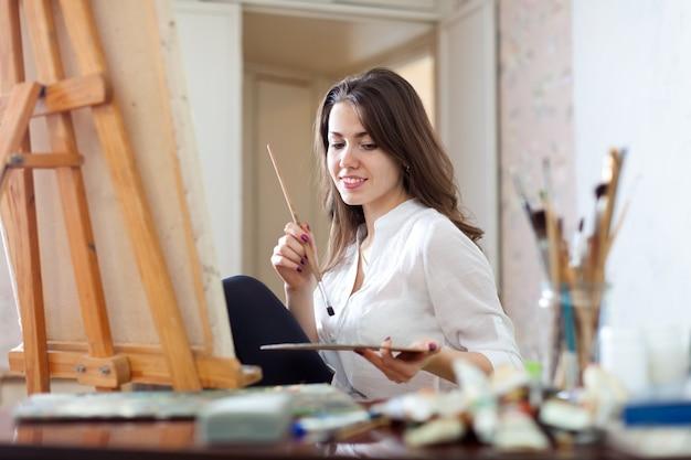 La fille peint sur toile avec des couleurs huile