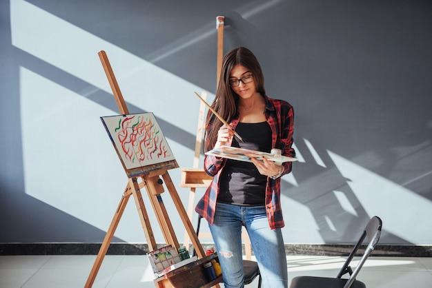 Fille peintre pensif créatif peint une image colorée sur toile avec des couleurs à l'huile en atelier.