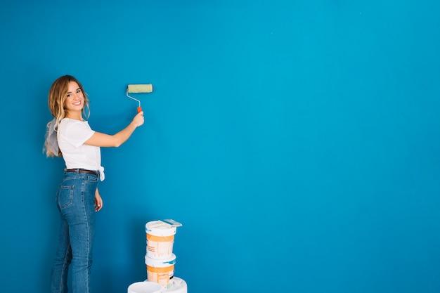 Fille peinture mur avec rouleau
