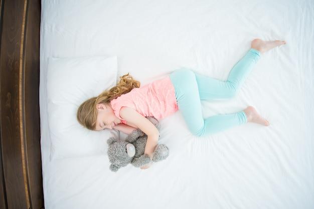 La fille avec une peluche dormant sur le lit. vue d'en-haut