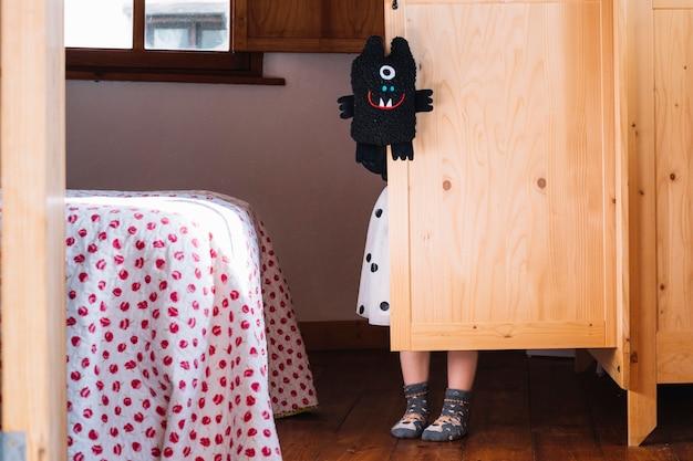 Fille avec peluche noire debout derrière le placard