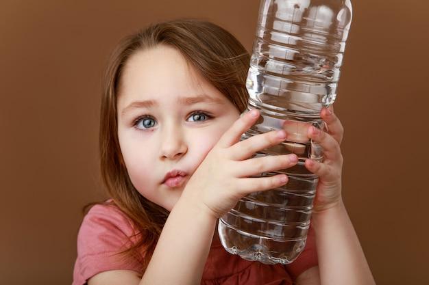 Fille penchant une bouteille d'eau sur sa joue